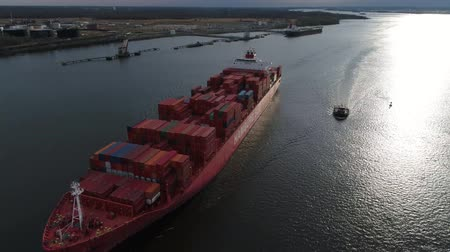 sending : Huge red loaded cargo freight container ship sailing slowly in ocean water in amazing 4k aerial seascape panorama view