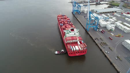 sending : Big red loaded freight cargo container ship arriving at industrial urban port in amazing 4k aerial drone seascape shot