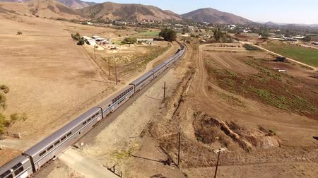 mozdony : Huge modern urban passenger train moving through dry desert canyon in sand steppe landscape in 4k aerial drone panorama