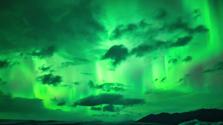 northern nature : Incredible 4k time lapse shot of bright neon green northern lights aurora borealis glowing in dark polar night sky
