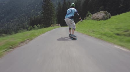 longboarder : Young professional skateboarder performs stunts riding longboard downhill country side road in amazing forest landscape
