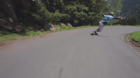 patenci : Professional young skateboarder performs stunts riding longboard downhill country side road in amazing forest landscape