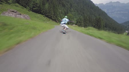 longboarder : Extreme first pov shot of young professional skateboarder performing stunts while riding loangboard in forest landscape