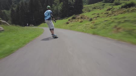 longboarder : Extreme first pov shot of professional young skateboarder performing stunts while riding loangboard in forest landscape