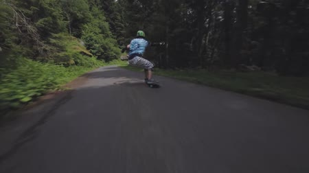 longboarder : Extreme first pov view on professional young skateboarder performing stunts while riding longboard in forest landscape
