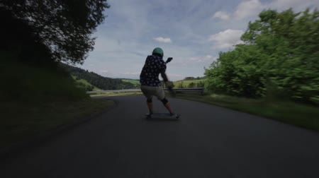 luge : Young male professional skateboarder performs dangerous stunts on country side landscape road in first person pov shot