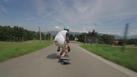 luge : Professional young male skateboarder performs dangerous stunts on country side landscape road in first person pov shot Stock Footage