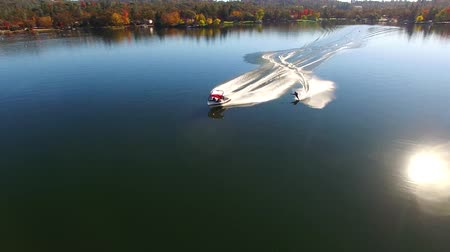 bezmotorové létání : 4k aerial view on professionl male athlete water skiing with motor boat in beautiful forest landscape in calm lake water Dostupné videozáznamy