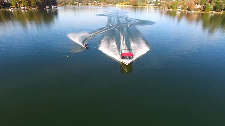 bezmotorové létání : Aerial 4k view on professionl male athlete water skiing with motor boat in beautiful forest landscape in calm lake water Dostupné videozáznamy