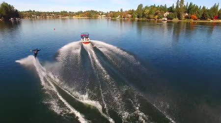 bezmotorové létání : Stunning 4k aerial view on professional male water skier gliding in calm blue lake water in forest park sunny landscape