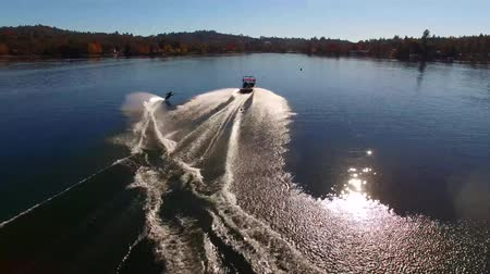 bezmotorové létání : Professional male water skier gliding in calm blue lake water in forest park sunny landscape in stunning 4k aerial view Dostupné videozáznamy