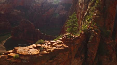 espetacular : Woman traveller tourist walking through red sand stone cliff mountain range canyon cave in amazing 4k aerial drone view Stock Footage