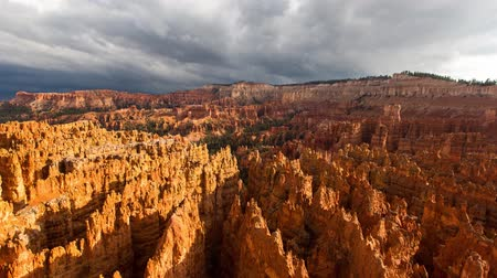 maravilha : Heavy fluffy grey rain clouds moving in sky over amazing red orange sand stone cliff mountain range desert canyon in 4k