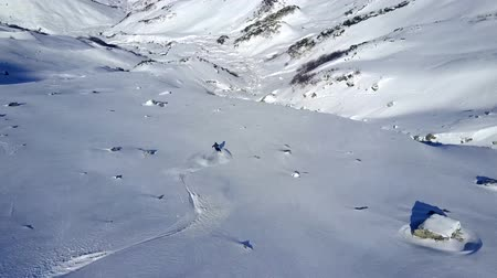 ledovec : 4k aerial drone view on lonely professional skier riding fast downhill on beautiful snowy mountain landscape empty hill