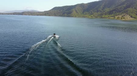 sportowiec : Beautiful 4k aerial drone view on person water skiing attached to motor boat in tropical ocean mountain skyline seascape Wideo