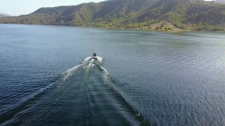 maravilhoso : Wonderful 4k aerial drone view on person water skiing attached to motor boat in tropical ocean mountain skyline seascape
