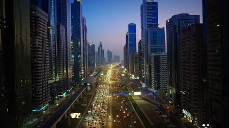 arabian sea : Fascinating aerial drone flight over busy evening highway road in big city modern architecture Dubai downtown cityscape
