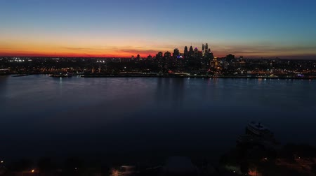 Fascinating 4k aerial drone view on bright orange evening sunset sky over dark light city Philadelphia by ocean seascape