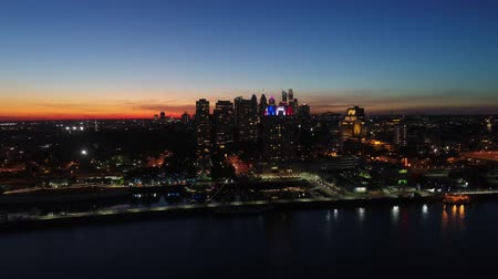 Spectacular 4k aerial drone view on bright orange evening sunset sky over dark illumination light city by ocean seascape