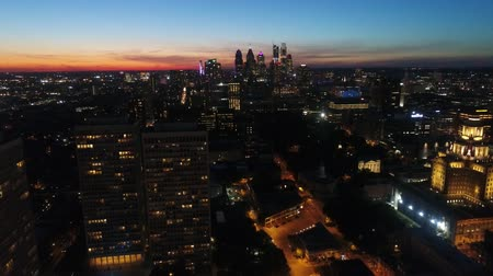 Impressive 4k aerial drone flyover in warm orange evening sunset sky over city bright night light illumination cityscape Stok Video