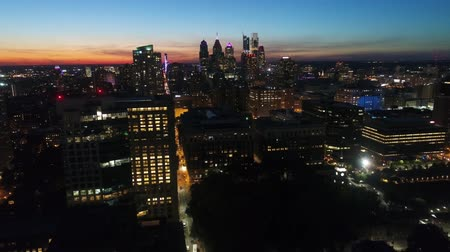 Warm orange evening sunset sky over city bright night light illumination cityscape in beautiful 4k aerial drone flyover