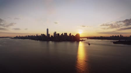 přímořská krajina : Fascinating drone aerial panorama flight in warm orange evening sunset sky over New York urban popular skyline cityscape