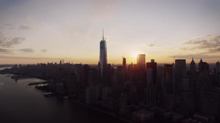 New York City modern skyline cityscape silhouette in warm evening orange sunset in amazing drone aerial panorama flyover