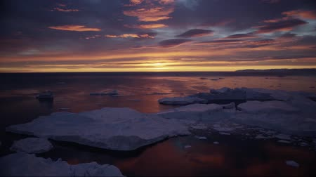 disko bay : Arctic nature landscape with icebergs in Greenland icefjord with midnight sun sunset Stock Footage