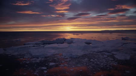 Arctic nature landscape with icebergs in Greenland icefjord with midnight sun sunset in the horizon. Aerial drone footage video of ice. Ilulissat Icefjord with icebergs from glacier. Stok Video