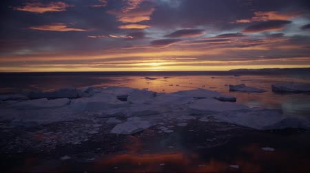 disko bay : Arctic nature landscape with icebergs in Greenland icefjord with midnight sun sunrise in the horizon. Aerial drone footage video of ice. Ilulissat Icefjord with icebergs from glacier.