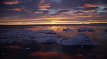 disko bay : Arctic nature landscape with icebergs in Greenland icefjord with midnight sun sunset  sunrise in the horizon. Aerial drone footage video of ice. Stock Footage