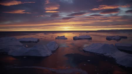 disko bay : landscape with icebergs in Greenland icefjord with midnight sun sunset sunrise in the horizon. Aerial drone footage video of ice. Ilulissat Icefjord with icebergs from glacier.