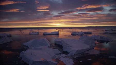 disko bay : nature landscape with icebergs in Greenland icefjord with midnight sun sunset  sunrise in the horizon. Aerial drone footage video of ice. Ilulissat Icefjord with icebergs from glacier.