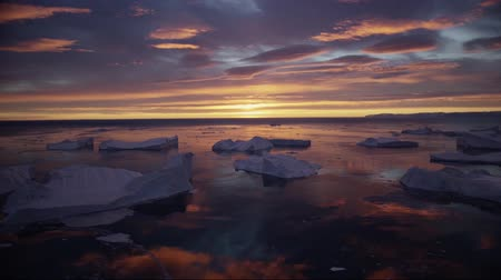 disko bay : Greenland icefjord with midnight sun sunset  sunrise in the horizon. Aerial drone footage video of ice. Ilulissat Icefjord with icebergs from glacier.
