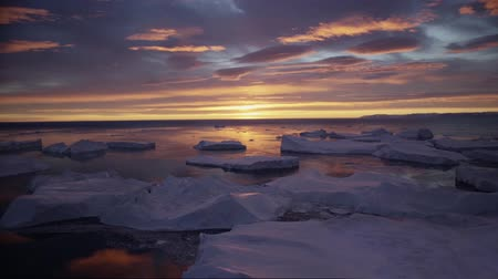 disko bay : Arctic landscape with icebergs in Greenland icefjord with midnight sun sunset  sunrise in the horizon. Aerial drone footage video of ice. Ilulissat Icefjord with icebergs from glacier.