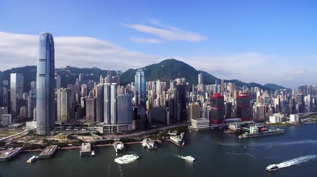 határkő : shooting from a drone, view from the sea at the skyscrapers of Hong Kong, against the backdrop of beautiful mountains Stock mozgókép