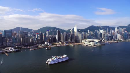drone flies over the sea, view of downtown, in the frame of skyscrapers against the backdrop of mountains, a huge metropolis of Hong Kong, a ship sails across the sea