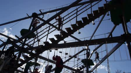plac zabaw : Families play on large gorilla climb ropes course silhouette 1