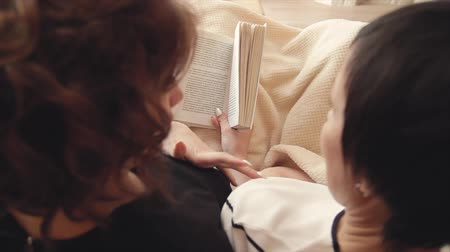 прижиматься : An adult daughter and her mother lie on the couch, read a book together, spend time together