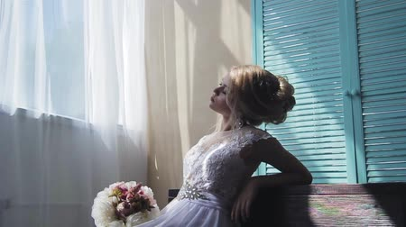 duygusallık : Very beautiful blonde with blue eyes in a white bride dress near a window with a bouquet of flowers
