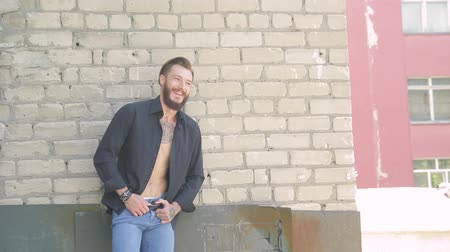 black and white : a handsome brutal man with a beard in jeans and a black T-shirt on the background of a gray brick wall
