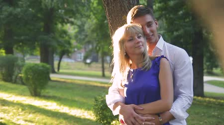 human heart : beautiful couple in love with a woman walking in a park on a bench kissing at sunset and loving each other, a blue dress and a white shirt with jeans Stock Footage
