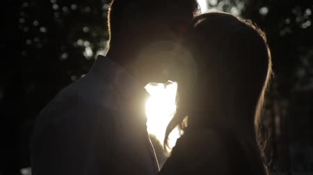 two hearts : beautiful couple in love with a woman walking in a park on a bench kissing at sunset and loving each other, a blue dress and a white shirt with jeans Stock Footage