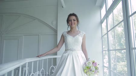 korzet : beautiful bride in a white dress in the studio on a background of a huge window