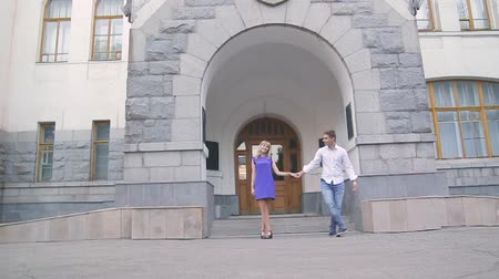 two hearts : loving young couple walking around town man in white shirt and girl in blue dress