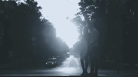 two hearts : a loving young couple standing at an automobile cross embraces and kisses in the backlight
