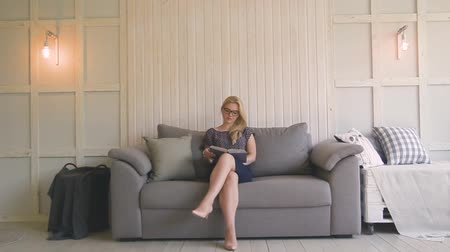 papelada : beautiful blond woman with glasses sits on the couch and throws up paper