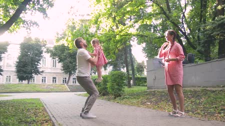 przyjęcie : young happy family with little beautiful baby with blue eyes walking in summer park at sunset.