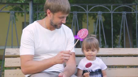 benzer : happy young father with a cute daughter on a bench with a candy in hands