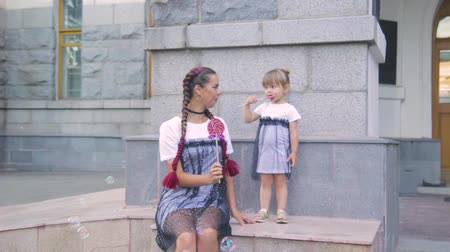 аналогичный : happy young mother with a cute daughter on a bench with a candy in hands in identical dresses